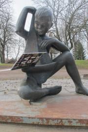 Kirjaston Rauhanpuistossa sijaitseva Jussi Vikaisen tekemä Toivo viettää kirjan ja ruusun päivää lukemalla Heli Laaksosen murteella kirjoittamaa aapista.