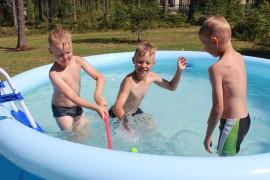 Eevert Lehtola, Miska Karppinen ja Ilari Lehtola viihtyvät uima-altaassa.