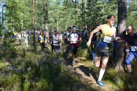 Mynämäen Antti Vainio veti miesten kovavauhtisen lähtöryhmän metsän siimekseen, takana hyvässä rytmissä muun muassa tuleva viestimestari Markku Elo (numero 1001). Kuva: Veijo Viitanen