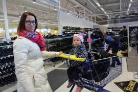 Reeta Nurmen mielestä Kenkä-Laakson myymälä sijaitsee nyt aikaisempaa paremmassa paikassa. Kärryissä 2,5-vuotias Hilma Heijari ja 4-kuukautinen Viljo Heijari.