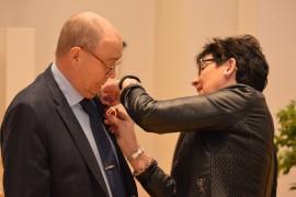 Kaupunginjohtajan sihteeri Pirjo Fredling kiinnitti kultaisen ansiomerkin työpäällikkö Pekka Askolan puvun rintamukseen. Kuva: Juhani Marttala