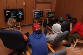 Yhteen nuokkarin huoneista oli viritelty kolme pelikonsolia. Niiden ääreen oli kokoontunut sekä pelaajia että yleisöä. Kuva: Hanna Hyttinen