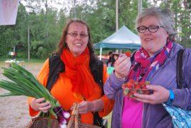 Sirke Lehtilä on ostanut vihanneksia ja Heljä Raitamäki maistelee mansikoita, jotka aikoo ostaa. Kuva: Jasmiina Haarala