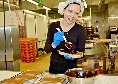 Kaija Lätt levittää suklaata gluteenittomien vuokaleivonnaisten päälle.
