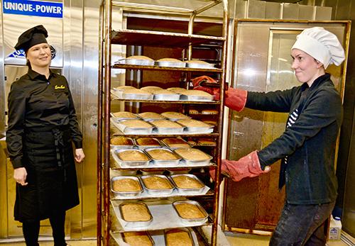 Tuotantopäällikkö Inga Heinonen seuraa, kun Liisa Nikula ottaa valmiita leivonnaisia ulos paistouunista.